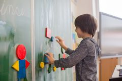 First grade child, learning math, shapes and colors at school. Standing in front of blackboard royalty free stock images