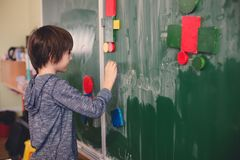 First grade child, learning math, shapes and colors at school. Standing in front of blackboard royalty free stock image