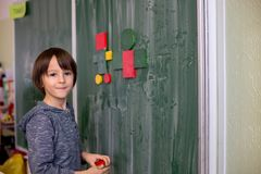 First grade child, learning math, shapes and colors at school. Standing in front of blackboard stock photography