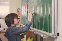First grade child, learning math, shapes and colors at school. Standing in front of blackboard royalty free stock photography