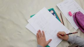First grade school girl practicing math drills at home. Using pencil and eraser stock footage