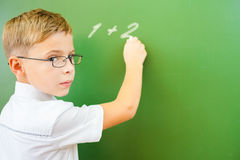 First grade schoolboy wrote on blackboard with chalk at classroom Stock Photos