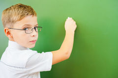 First grade schoolboy wrote on blackboard with chalk at classroom Royalty Free Stock Image