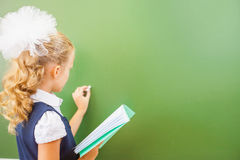 First grade schoolgirl wrote on blackboard with chalk at classroom Stock Photography