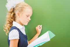 First grade schoolgirl wrote on blackboard with chalk at classroom Stock Image