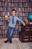 First-grader boy with a board in a library Royalty Free Stock Photography