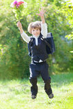 First-grader boy with bouquet and backpack is jamping Stock Image