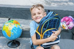 First-grader is sitting with a backpack on the doorstep of the school. bouquet and globe. the first call. end of the school year Royalty Free Stock Photography