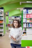 First grader choosing books in bookstore. Cute girl reading books at store stock images
