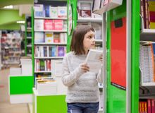Cute girl with book at store. First grader choosing books in bookstore for school royalty free stock photos