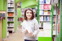 Cute girl reading books at store. First grader choosing books in bookstore for school royalty free stock photos