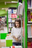 Girl  of 8   years  choosing books in   bookstore. First grader  choosing   books in   bookstore for school Royalty Free Stock Photo