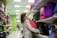 First grader choosing briefcase in store. Portrait of girl of 8 years in shop choosing briefcase for school royalty free stock photography