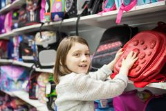 First grader choosing briefcase in store for school. Portrait of girl of 8 years in shop choosing briefcase for school royalty free stock image