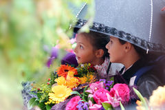 First grader girl and boy under an umbrella at  school Royalty Free Stock Images