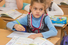 First-grader at lesson of mathematics solves examples and look at the board Stock Photos