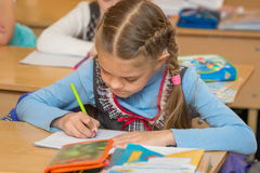 First-grader at lesson of mathematics to solve the examples notebook Stock Images