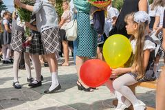 The first-grader looks sadly at a meeting of girlfriends on the feast of the first of September. Anana, Russia - September 1, 2017: The first-grader looks sadly Royalty Free Stock Photo