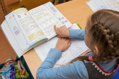 First grader reads the task in the textbook running his finger under the text. Anapa, Russia - February 28, 2017: First grader reads the task in the textbook Stock Photos