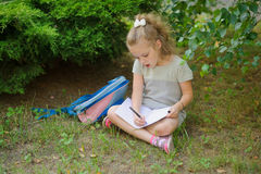 First grader sits having crossed legs under a tree and does homework. Royalty Free Stock Images