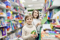 First graders choosing books in bookstore. Portrait of girls of 8 and 6 years in shop choosing books stock photography