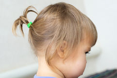 First hair style: tiny ponytail, profile of baby girl Stock Photo