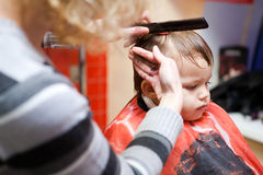 First hairstyle. Little boy in a hairdressing salon. The first hairstyle Stock Images