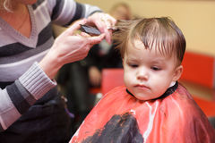 First hairstyle. Little boy in a hairdressing salon. The first hairstyle Royalty Free Stock Photography