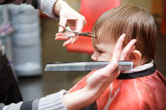 First hairstyle. Little boy in a hairdressing salon. The first hairstyle Stock Photos