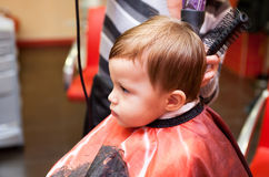 First hairstyle. Little boy in a hairdressing salon. The first hairstyle Stock Photo