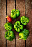Green peppers on wooden plank Royalty Free Stock Image