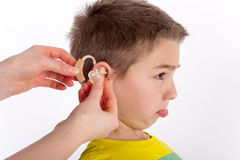 The first hearing aid. Small boy trying his first hearing aid and not too happy with it. Focused on the hand and the hearing aid Stock Image