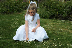 First holy communion. Portrait of a girl in a white dress  picking flowers in the garden on his day of first holy communion Stock Images