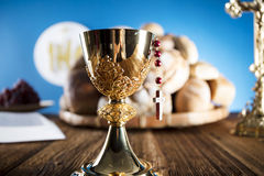 First Holy Communion. Catholic religion theme. Crucifix, Bible, bread on rustic wooden table and blue background stock image