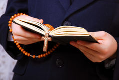 First holy communion-prayer book. Hands of the boy going to the First Holy Communion holding prayer book and a rosary Royalty Free Stock Photos