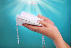 The first holy communion with prayer book in hands. Hands of a girl going to the first holy communion holding prayer book with rosary on blue background Stock Photos