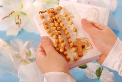 First holy communion-prayer book and rosary. Hands of the girl going to the First Holy Communion keeping a  prayer book and a  rosary Royalty Free Stock Photos