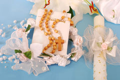 First holy communion-prayer book and rosary. Prayer book , wooden rosary and candle for first holy communion on blue background Royalty Free Stock Photography