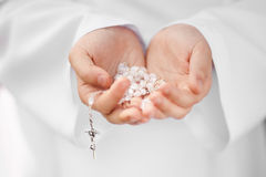 First Holy Communion rosary detail. First Holy Communion concept - close up on rosary on child's hands Royalty Free Stock Photography