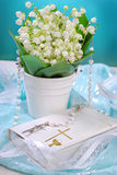 The first holy communion still life. Bunch of fresh lily of the valley flowers and white prayer book with rosary on blue background for the first holy communion Stock Image