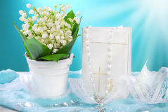 The first holy communion still life. Bunch of fresh lily of the valley flowers and white prayer book with rosary on blue background for the first holy communion Royalty Free Stock Photos