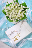 The first holy communion still life. Bunch of fresh lily of the valley flowers and white prayer book with rosary on blue background for the first holy communion Stock Photo