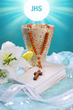 The first holy communion still life. With chalice,wooden rosary, prayer book and lily on blue background Stock Image