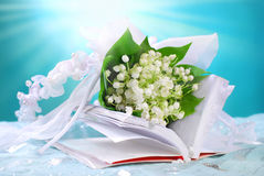 The first holy communion still life. With opened prayer book and bunch of lily of the valley on blue background Royalty Free Stock Photos