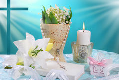 The first holy communion still life. With prayer book,candle and flowers on blue background Stock Photos