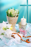 The first holy communion still life. With prayer book,rosary,candle and flowers on blue background Stock Photo
