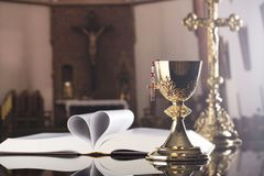 First holy communion theme. Catholic concept background. The Cross, Holy Bible, rosary and golden chalice on the altar.  Place for typography or logo Royalty Free Stock Image