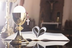 First holy communion theme. Catholic concept background. The Cross, Holy Bible, rosary and golden chalice on the altar.  Place for typography or logo Stock Photography