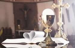 First holy communion theme. Catholic concept background. The Cross, Holy Bible, rosary and golden chalice on the altar.  Place for typography or logo Stock Image