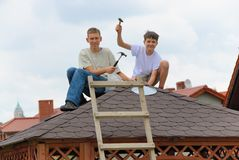 First job. Teenagers learn how to put roof shingles